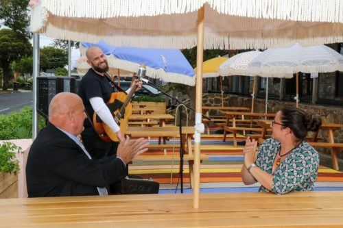 Cr David Asker and Ginevra Hosking applaud musician Simon Levick at the Norman Ave shops, Frankston South.